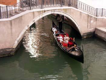 Gondola passa sotto un ponte in Campo Manin a Venezia